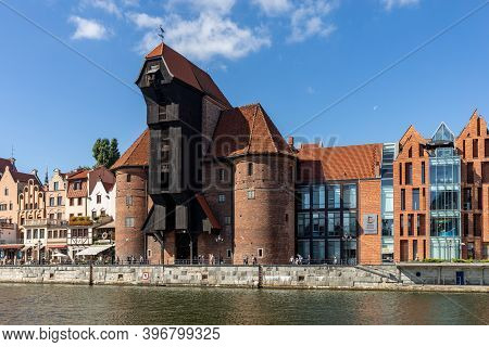 Gdansk, Poland - Sept 9, 2020: The Largest Medieval Port Crane In Europe And Historic Buildings On T