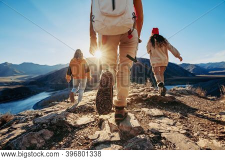 Three Young Tourists Hikers Walks Against Sunset Mountains And River