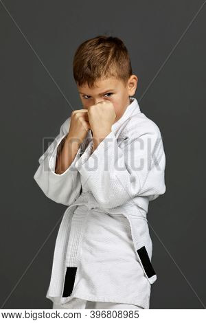 Little Child Boy In A White Karate Kimono Over Gray Background. Karate Fighter Ready To Fight.
