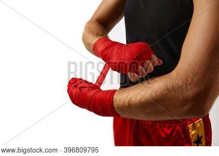 Sporty Man Wraps His Hands In Red Sports Bandages Before Training. Close-up