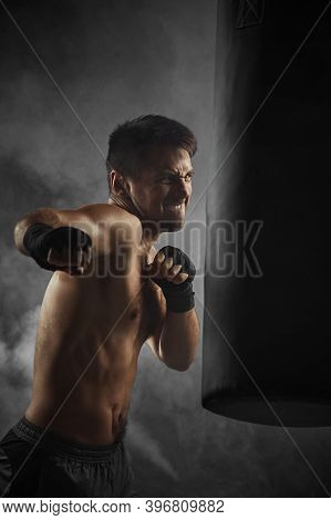Aggressive Boxer In Black Boxing Wraps Punching In Boxing Bag On Dark Background With Smoke