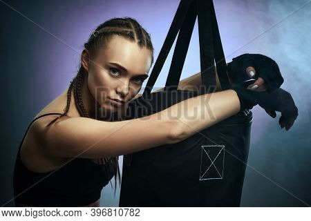 Beautiful Fit Brunette Woman In Sportswear With Boxing Bandages Near Bag On Dark Background With Smo