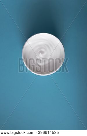 Close Up Of White Beauty Cream Or Yoghurt On Light Blue Background. Place For Text.