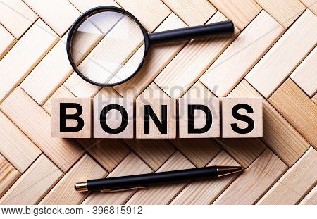Wooden Cubes With The Word Bonds Stand On A Wooden Background Between A Magnifying Glass And A Handl