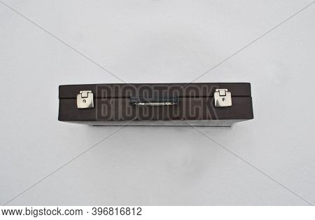 Top View Of A Closed Brown Briefcase. Briefcase On A White Background. The Case Was Stuck In The Sno
