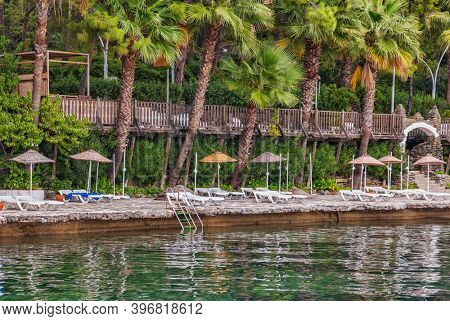 View of the stones beach with palm trees from the side sea. Marmaris. Turkey