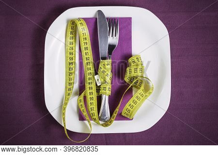 Knife And Fork With Tape Measure. Conceptual Of Eating Disorder, Diet, Feeding