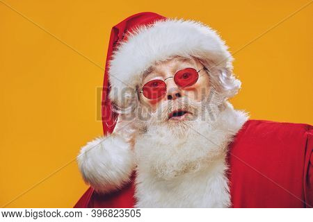 Santa Claus is surprised. Portrait of a traditional Santa Claus on a yellow background. Copy space.