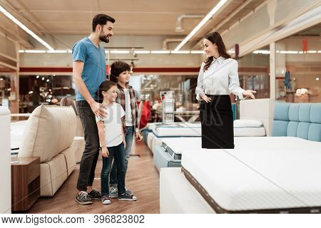 Young Girl Consultant Demonstrates Orthopedic Mattress To Young Father With Children In Furniture St