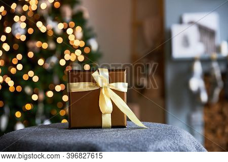 Wrapped Gift For A New Background And Christmas In Gold Paper Against The Background Of Garlands Of