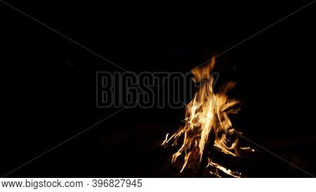A Fire Is Burning. People Make Marshmallows. Sparks Fly From The Fire. The Embers Glow. People Enjoy