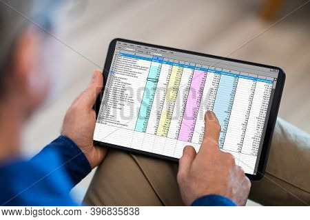 Man Holding Tablet With Online Spreadsheet Data Document