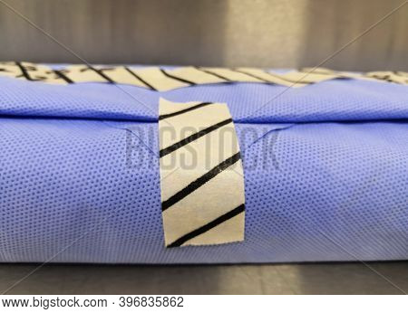Wrapped Surgical Instrument Pack. Pack With Drape Sheet And Indicator Tape. Selective Focus