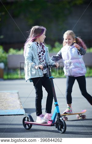 Active Girls Riding Kick Scooter And Skateboard In Skate Park. Children Having Free Time Playing. Th