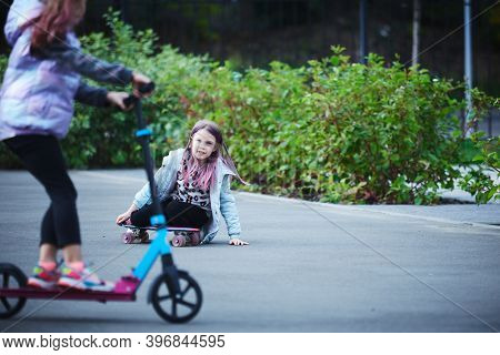 Active Girls Riding Kick Scooter In Skate Park.
