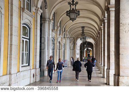 Lisbon, Portugal - June 4, 2018: People Visit Shaded Arcades Of Comercio Square (praca Comercio) In