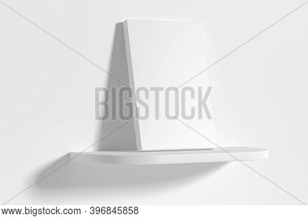 Blank White Empty Rectangular Poster On White Rounded Shelf Leaning At Empty White Wall, Diagonal Vi
