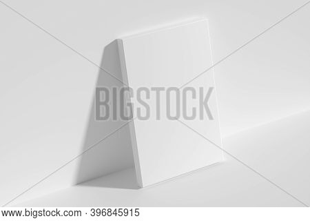 Blank White Empty Rectangular Poster On Floor Leaning At Empty White Wall, Top Diagonal View, White