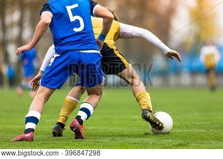 Adult Soccer Players Compete In A Tournament Match. Footballers In A Duel. Boys Kicking Soccer Ball