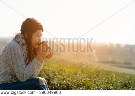 Asian Lifestyle Women Wearing Sweater, Sitting And Drinking Hot Coffee Or Tea Relax Outdoor In The S