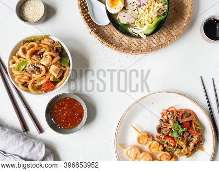 Set Asian Food - Ramen Soup, Grilled Shrimp, Stir Fry Vegetables And Udon With Seafood On A White Ba