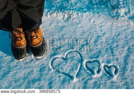 Love Winter Concept- Feet In Snow Boots And Heart In Nature
