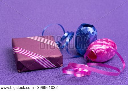 Gift In A Violet Box And A Decorative Ribbon Next To A Violet Background New Years Background