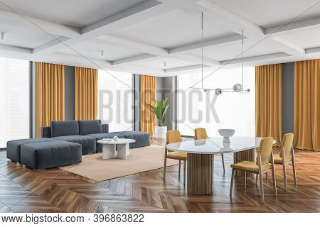 Big Living Room With Yellow Chairs, White Table And Grey Sofa, Side View. Large Windows In Big Hall