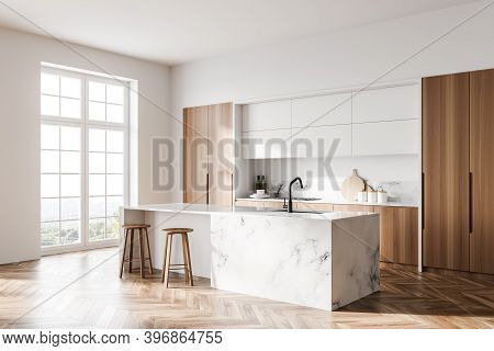 Corner Of Modern Kitchen With White Walls, Wooden Floor And Marble Bar With Stools. Window With Blur