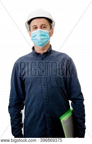 Middle Aged Contractor Or Architect  Holding A Notepad, Wearing Protective Helmet And Face  Mask  Pr