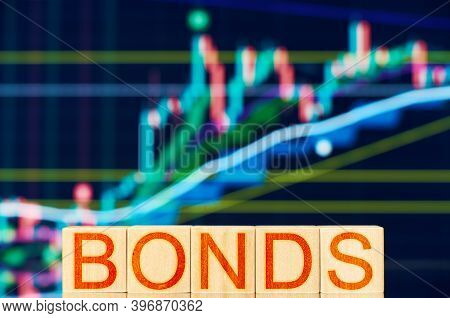 Bonds. Wooden Blocks With The Inscription Bonds On The Background Of The Stock Chart