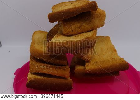 Stack Of Dry Toast On Plastics Plate. Close Up Pile Of Toasted Bread Slices. Toast Loaf On White Bac