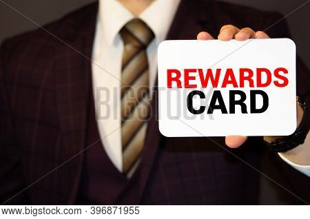 Businessman Putting A Card With Text Reward Performance In The Pocket.