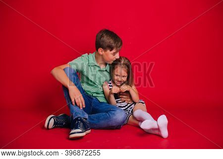 Brother And Sister. Little Girl In A Striped Dress With A Boy In A Green Shirt On A Red Background.