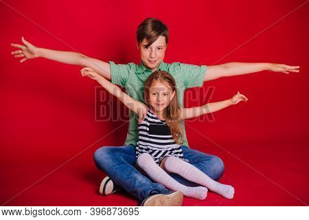 Brother And Sister Hold Their Arms Out To The Sides. Little Girl In A Striped Dress With A Boy In A
