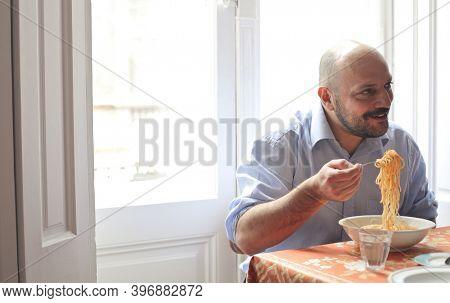 man eats pasta at home
