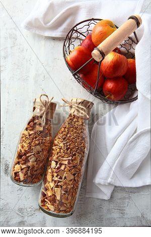 Granola In Glass Bottles On A Light Background. Red Apples In A Metal Basket. Muesli In Glass Bottle