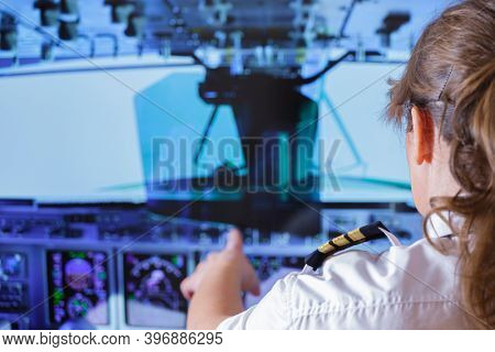 Beautiful woman pilot wearing uniform with epauletes changes the autopilot settings in the cockpit of a flying airplane