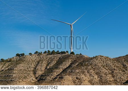 Isolated Wind Turbine On Top Of A Hill With Semi-desert Landscape