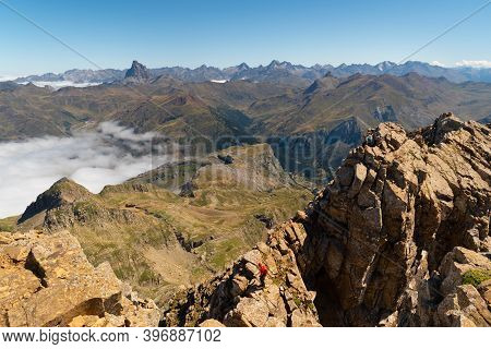 Two Anonymous Climbers Reaching Aspe Peak In The Pyrenees With Peaks And Mountains On The Spanish Si