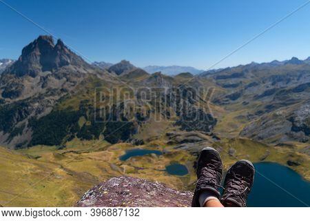 Focused Boots Of A Hiker Atop Ayous Peak With Unfocused Views Of Ayous Mountain Lake And The Pyrenee