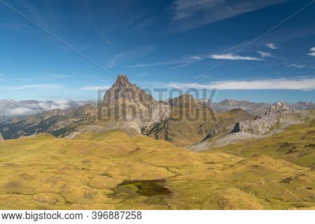 Meadows With Mountains Around And The Midi D'ossau Peak In The Pyrenees On A Clear Day With Some Sma