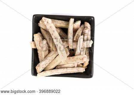 Dehydrated Taro Snack Sticks In A Black Bowl Isolated Over White Top Down View