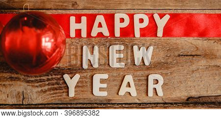 Happy New Year Inscription In Wooden Letters On A Wooden Table. The Word Happy On The Red Ribbon. Ne