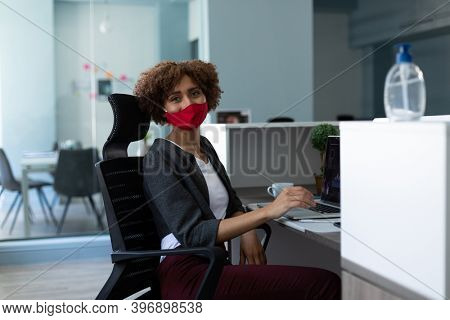 Mixed race woman wearing face mask in office. looking at the camera and smiling. hygiene in workplace during coronavirus covid 19 pandemic.