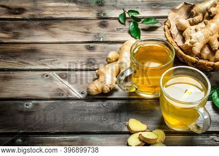 Ginger Tea And Fresh Ginger In The Basket. On Wooden Background