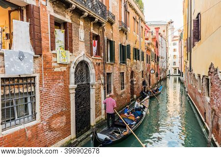 Venice, Italy - September 23, 2019: Gondolier Carries Tourists On Gondola In Canal Of Venice, Italy.