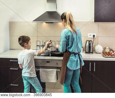 Mother and son preparing food in the kitchen. Family enjoying weekend, stay home.