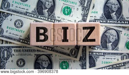 Concept Word 'biz' On Cubes On A Beautiful Background From Dollar Bills. Business And Biz Concept.