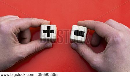 Wooden Cubes In Hands On A Red Background With Plus And Minus. Business Concept